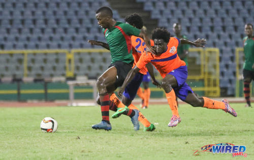 Photo: San Juan Jabloteh forward Jamal Gay (centre) holds off a Club Sando defender during Pro League action at the Hasely Crawford Stadium on 9 December 2016. (Courtesy Sean Morrison/Wired868)
