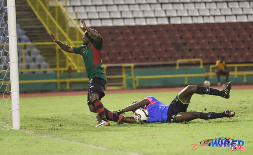 Photo: San Juan Jabloteh attacker Kennedy Hinkson (left) trips over Club Sando goalkeeper Kelvin Henry and is about to clatter into the upright during Pro League action at the Hasely Crawford Stadium on 9 December 2016. (Courtesy Sean Morrison/Wired868)