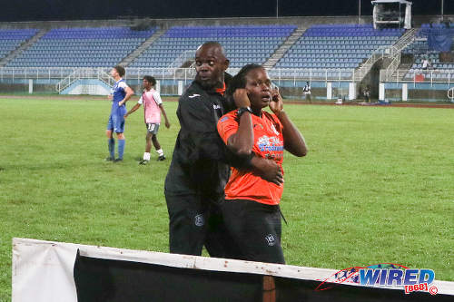 Photo: Naparima College paramedic Kaleisha Delpeche (right) is restrained by the team's goalkeeper coach, Brian James, following a scuffle with Presentation College (San Fernando) paramedic Nathalie Charles after the Big Four final at the Ato Boldon Stadium, Couva on 12 December 2016. (Courtesy Chevaughn Christopher/Wired868)