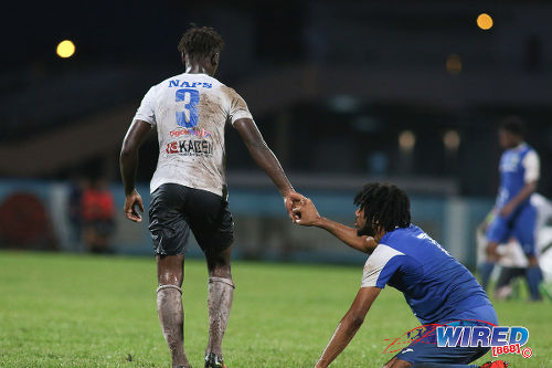 Photo: Naparima College left back Khris Stroud (left) offers a hand to Presentation College (San Fernando) attacker Nion Lammy after the Big Four final at the Ato Boldon Stadium, Couva on 12 December 2016. (Courtesy Chevaughn Christopher/Wired868)