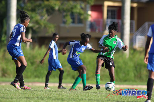 Photo: A Fyzabad Anglican Secondary player (centre) tries to play the ball around Penal Secondary player Elise Simone during the Girls South Zone Knockout final at the Mannie Ramjohn Stadium training ground on 2 December 2016. (Courtesy Chevaughn Christopher/Wired868)
