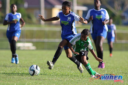 Photo: Penal Secondary attacker Petrice Tyson (right) tumbles under a challenge from a Fyzabad Anglican Secondary player during the Girls South Zone Knockout final at the Mannie Ramjohn Stadium training ground on 2 December 2016. (Courtesy Chevaughn Christopher/Wired868)