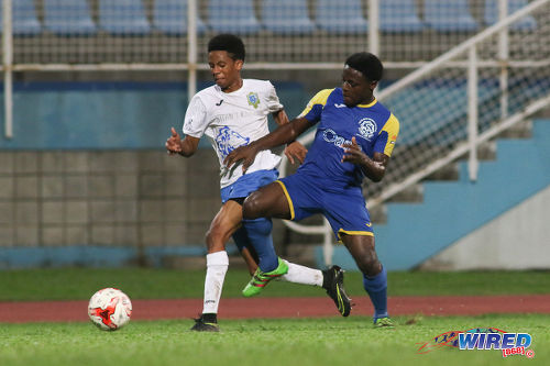 Photo: Presentation College (San Fernando) winger Jordan Riley (left) tries to wriggle from Shiva Boys Hindu College flanker Quinn Rodney during the SSFL Big Four semifinals on 9 December 2016 at the Ato Boldon Stadium in Couva. (Courtesy Chevaughn Christopher/Wired868)