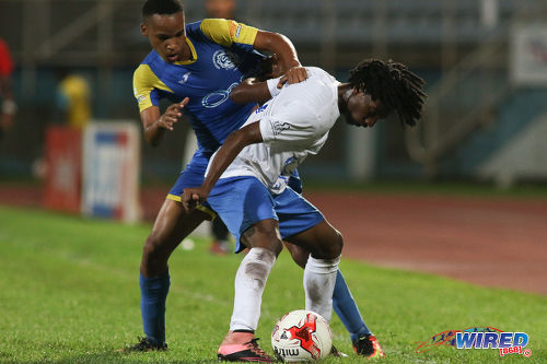 Photo: Presentation College (San Fernando) right back Mylz Barrington (right) holds off Shiva Boys Hindu College winger Ronaldo Edwards during the SSFL Big Four semifinals on 9 December 2016 at the Ato Boldon Stadium in Couva. (Courtesy Chevaughn Christopher/Wired868)