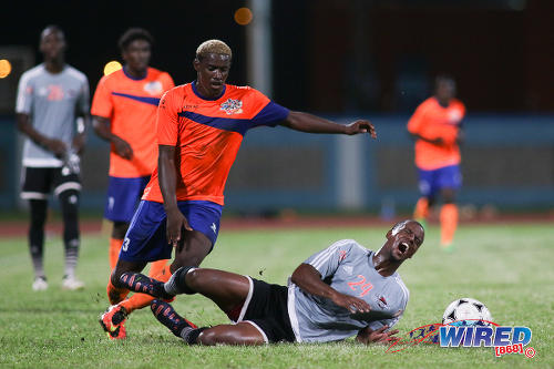 Photo: Club Sando attacker Akee Roach (left) looks to glide past fallen Central FC defender Kevon Villaroel during Pro League action at the Ato Boldon Stadium on 16 December 2016. (Courtesy Chevaughn Christopher/Wired868)