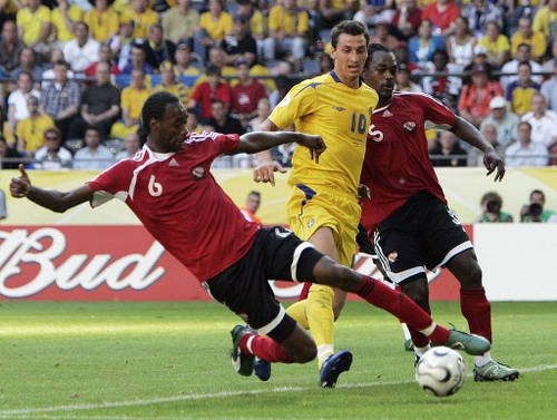 Photo: Trinidad and Tobago defender Dennis Lawrence (left) tackles Sweden forward Zlatan Ibrahimovic (centre) during the 2006 World Cup at the Dortmund stadium on 10 June 2016. Looking on is Brent Sancho. (Copyright AFP 2016/Sven Nackstrand)