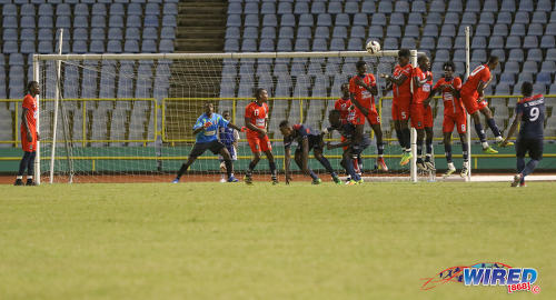 Photo: Morvant Caledonia United goalkeeper Marvin Phillip (second from left) senses danger as Defence Force striker Devorn Jorsling (far right) lofts his free kick over the defensive wall during Pro League action at the Hasely Crawford Stadium on 17 January 2017. (Courtesy Sean Morrison/Wired868)