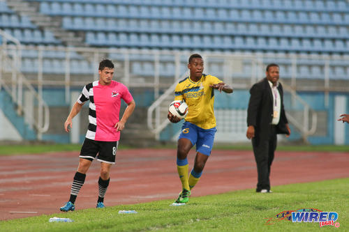 Photo: Defence Force right back Rodell Elcock (centre) prepares to take a throw in while Central FC midfielder Sean De Silva (left) looks on during Pro League action at the Ato Boldon Stadium, Couva on 24 January 2017. Keeping an eye on things is Defence Force coach Marvin Gordon. (Courtesy Chevaughn Christopher/Wired868)