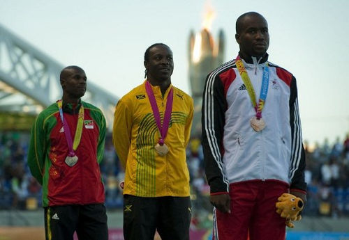 Photo: Trinidad and Tobago's bronze medallist Emmanuel Callender (right), Jamaica's gold medallist Lerone Clarke (centre) and Saints Kitts and Nevis' Silver medallist Kim Collins take to the podium after the 100m final of the Guadalajara 2011 XVI Pan American Games in Guadalajara, Mexico on 25 October 2011. (Copyright AFP 2017/Luis Acosta)