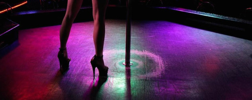 Photo: A pole dancer prepares to start her routine. (Courtesy Literary Hub)