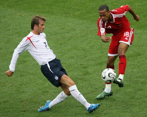 Photo: Trinidad and Tobago midfielder Densill Theobald (right) challenges England captain David Beckham during a Group B contest in the 2006 World Cup at the Franken Stadium, Nuremberg on 15 June 2006.  (Copyright AFP 2017/Valery Hache)
