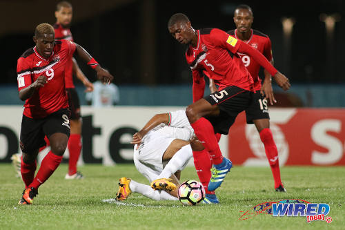 Photo: Trinidad and Tobago midfielder Hashim Arcia (right) tries to sidestep a Surinamese tackle while teammate Akeem Roach (left) tries to make a run during 2017 Gold Cup playoff action at the Ato Boldon Stadium, Couva on 4 January 2017. (Courtesy Chevaughn Christopher/Wired868)