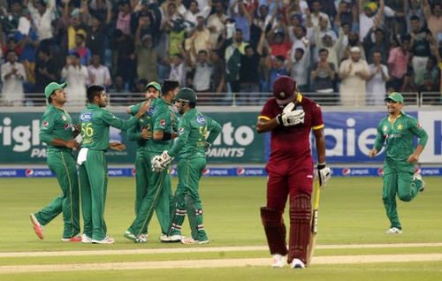 Photo: West Indies batsman Andre Fletcher (centre) heads back to the pavilion after falling victim to Pakistan bowler Imad Wasim (third from left) during the first T20I match at the Dubai International Cricket Stadium on 23 September 2016.  (Copyright AFP 2017/Karim Sahib)