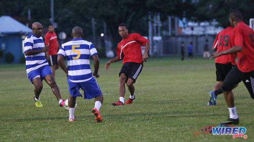 Photo: Invitational XI midfielder Densill Theobald (centre) passes between Wired868 players Caleb De Souza (far left) and Roger Henry (second from left) in the Wired868 Football Festival V at UWI admin ground on 7 January 2017. (Courtesy Sean Morrison/Wired868)