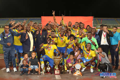 Photo: Defence Force striker Devorn Jorsling (stooping, second from right) and his teammates celebrate after retaining their Pro Bowl title at the Ato Boldon Stadium on 19 February 2017. Defence Force defeated Central FC 5-3 on kicks from the penalty spot after a 2-2 tie. (Courtesy Sean Morrison/Wired868)