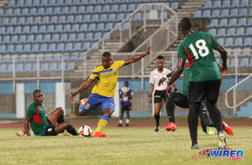 Photo: Defence Force midfielder Chris Durity (centre) goes for goal while Club Sando midfielder Keithy Simpson (far left) and referee Crystal Sobers (centre) look on during Digicel Pro Bowl quarterfinal action at the Ato Boldon Stadium in Couva on 9 February 2017. (Courtesy Sean Morrison/Wired868)