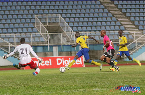 Photo: Defence Force striker Jamille Boatswain (second from left) squeezes his shot past Central FC goalkeeper Jan-Michael Williams (left) while defender Julius James (second from right) and Jerwyn Balthazar look on during the Pro Bowl final at the Ato Boldon Stadium on 19 February 2017. Defence Force won 5-3 on kicks from the penalty mark after a 2-2 draw. (Courtesy Sean Morrison/Wired868)