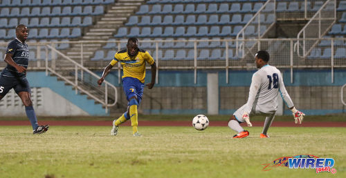 Photo: Defence Force striker Jamille Boatswain (centre) prepares to steer his hattrick goal past Police FC goalkeeper Adrian Foncette (right) during the Pro Bowl semifinals at the Ato Boldon Stadium on 12 February 2017. Defence Force won 4-0. (Courtesy Sean Morrison/Wired868)