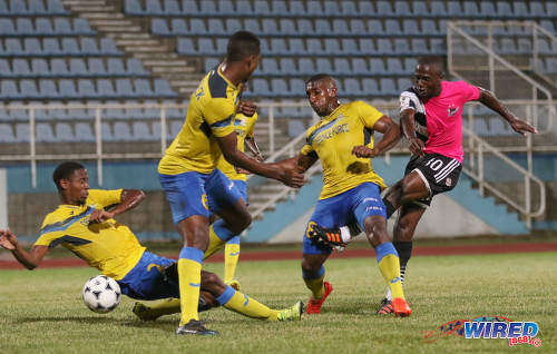 Photo: Central FC playmaker Keron Cummings (right) is closed down by Defence Force players (from right) Chris Durity, Rodell Elcock and Justin Garcia during the Pro Bowl final at the Ato Boldon Stadium on 19 February 2017. Defence Force won 5-3 on kicks from the penalty mark after a 2-2 draw. (Courtesy Sean Morrison/Wired868)
