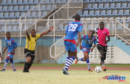Photo: Referee Rashby McFee (second from left) motions to play on as Central FC attacker Rundell Winchester (far right) runs at the St Ann's Rangers defence during Digicel Pro Bowl quarterfinal action at the Ato Boldon Stadium in Couva on 9 February 2017. (Courtesy Sean Morrison/Wired868)