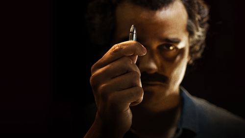 Photo: An actor playing late Colombian drug lord Pablo Escobar gestures with a bullet during the Netflix series, Narcos.
