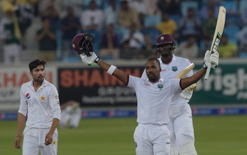 Photo: West Indies batsman Darren Bravo (right) raises his bat and helmet to celebrate a century against Pakistan as team captain Jason Holder (back) and Pakistani bowler Mohammad Amir look on during the final day of the first day-night Test between Pakistan and the West Indies at the Dubai International Cricket Stadium in the Gulf Emirate on 17 October 2016. (Copyright AFP 2017/Aamir Qureshi)