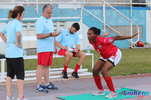 Photo: Trinidad and Tobago Women's National Senior Team assistant coach Elisabetta Bavagnoli (far left) and an unnamed fitness trainer (centre) and goalkeeping coach help a national player through her routine during practice at the Ato Boldon Stadium, Couva on 1 February 2017. (Courtesy Sean Morrison/Wired868)