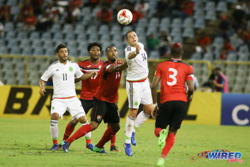 Photo: Mexico forward Javier Hernandez (second from right) tries to reach the ball while teammate Carlos Vela (far left) watches during 2018 World Cup qualifying action at the Port of Spain on 28 March 2017. Looking on are Trinidad and Tobago players (from right) Joevin Jones, Andre Boucaud and Mekeil Williams. (Courtesy Chevaughn Christopher/Wired868)