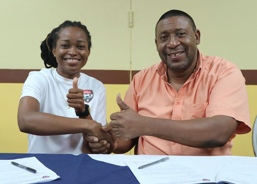 Photo: Trinidad and Tobago Women's National Senior Team midfielder Dernelle Mascall (left) gets a one year retainer contract from TTFA president David John-Williams. (Copyright TTFA Media)