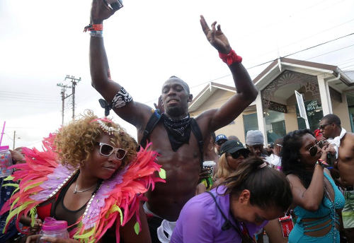 Photo: Jamaica sprint star and global sport icon Usain Bolt (centre) enjoys himself during the 2017 Carnival celebrations. (Copyright UK Sun)