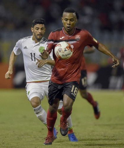 Photo: Trinidad and Tobago defender Curtis Gonzales (right) keeps the ball from Mexico attacker Carlos Vela during their Russia 2018 FIFA World Cup qualifying action at the Hasely Crawford Stadium in Port of Spain on 28 March 2017. (Copyright AFP 2017/Alfredo Estrella)