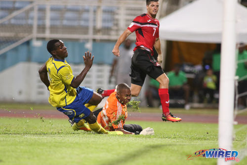 Photo: Trinidad and Tobago midfielder Sean De Silva (right) beats Barbados goalkeeper Dario Weir (centre) and a retreating defender but not the upright during international friendly action at the Ato Boldon Stadium in Couva on 10 March 2017.  Trinidad and Tobago won 2-0.  (Courtesy Chevaughn Christopher/Wired868)