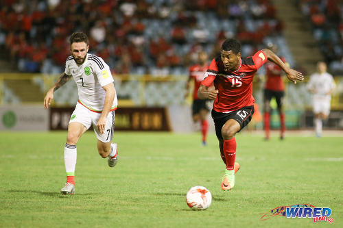Photo: Trinidad and Tobago forward Willis Plaza (right) runs at Mexico winger Miguel Layun Mexico forward Javier Hernandez (right) tries unsuccessfully to evade a tackle from Trinidad and Tobago midfielder Kevan George during 2018 FIFA World Cup qualifying action at the Hasely Crawford Stadium in Port of Spain on 28 March 2017. (Courtesy Chevaughn Christopher/Wired868)