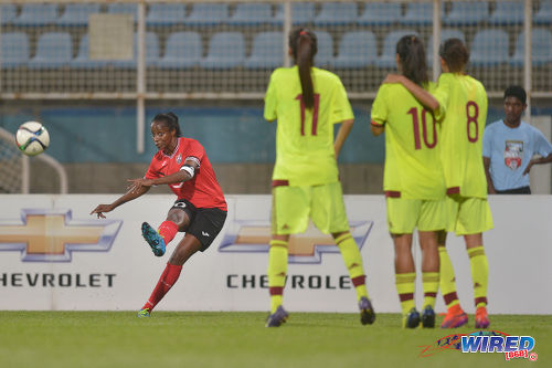 Photo: Trinidad and Tobago captain and attacker Tasha St Louis (left) curls a free kick towards goal during international friendly action against Venezuela at the Ato Boldon Stadium in Couva on 29 March 2017. Venezuela won 3-1. (Courtesy Chevaughn Christopher/Wired868)