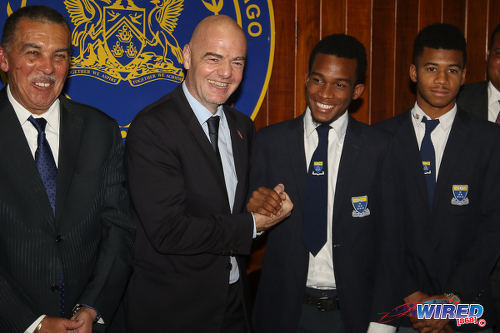 Photo: FIFA president Gianni Infantino (second from left) greets Fatima College captain Keyon Williams (second from right) while his teammate Stephon Marcano (far right) and Trinidad and Tobago President Anthony Carmona look on at President's House in St Ann's on 10 April 2017. (Courtesy Sean Morrison/Wired868)