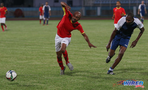 "Photo: DJ and soca artiste Jason ""JW"" Williams (left) tries to keep his balance after a challenge from former World Cup 2006 defender Dennis Lawrence (centre) sets a screen during an exhibition match at the Ato Boldon Stadium in Couva on 10 April 2017. (Courtesy Sean Morrison/Wired868)"