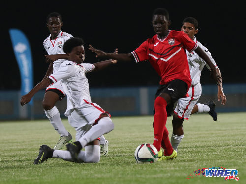 Photo: Trinidad and Tobago National Under-15 midfielder Jabari Lee (right) tries to evade a challenge from Republic Bank XI midfielder Randy Antoine during action at the Ato Boldon Stadium on 15 April 2017. (Courtesy Sean Morrison/Wired868)