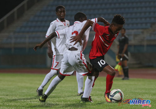 Photo: Trinidad and Tobago National Under-15 playmaker Josiah Edwards (right) tries to escape from Republic Bank XI defender Nathan Guy (centre) while his teammate Keron Manswell looks on during action at the Ato Boldon Stadium on 15 April 2017. (Courtesy Sean Morrison/Wired868)