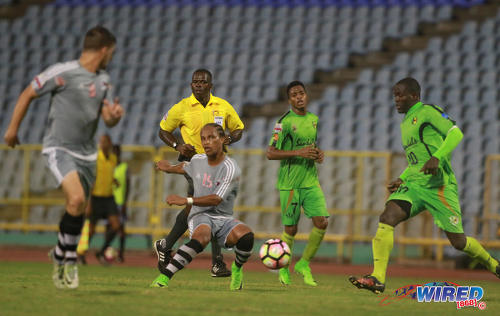 """Photo: Central FC midfielder Nathaniel """"Spanish"""" Garcia (centre) tries to caress a pass into the path of teammate Sean De Silva (far left) during 2017 Caribbean Club Championship action at the Hasely Crawford Stadium on 14 May 2017. Looking on (from right) are Grenades FC players Rakeem Henry and Nazir McBurnette and referee Sherwin Moore. (Courtesy Nicholas Bhajan/Wired868)"""