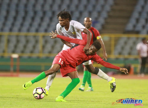 Photo: San Juan Jabloteh attacker Julio Noel (foreground) tries to hold off a challenge from a Racing Club opponent during 2017 Caribbean Club Championship action at the Hasely Crawford Stadium on 14 May 2017. Jabloteh won 2-0. (Courtesy Nicholas Bhajan/Wired868)