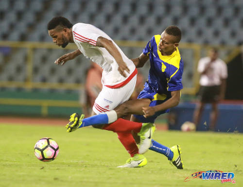 Photo: Portmore United winger Cleon Pryce (left) tries to escape from a challenge by a Racing Club defender during Caribbean Club Championship action at the Hasely Crawford Stadium on 16 May 2017. (Courtesy Nicholas Bhajan/Wired868)