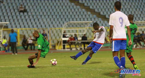 Photo: Portmore United captain and midfielder Ewan Grandison (centre) hammers home the equalising goal past San Juan Jabloteh defender Akeem Benjamin (left) during 2017 Caribbean Club Championship action at the Hasely Crawford Stadium on 18 May 2017. Jabloteh will meet Cibao FC from 8pm in Sunday's final. (Courtesy Sean Morrison/Wired868)