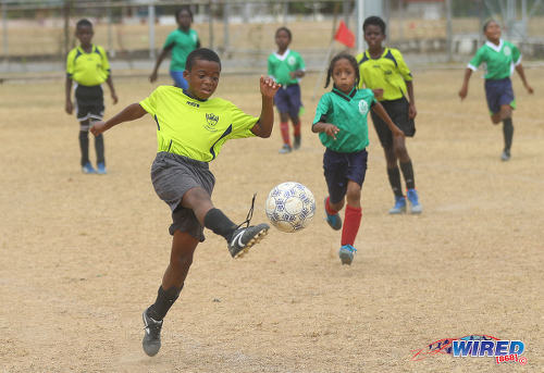 Photo: An Adrenaline FA player (left) clears the ball during RBNYL Under-11 action against Febeau Government Primary at Constantine Park in Macoya on 6 May 2017. (Courtesy Sean Morrison/Wired868)
