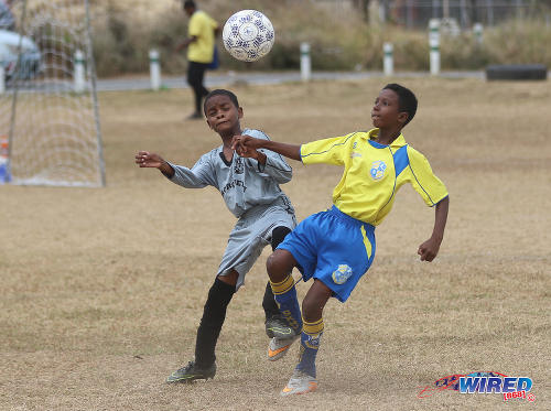 Photo: A Defence Force (right) and Cunupia Extreme player challenge the ball during RBNYL Under-11 action at Constantine Park in Macoya on 6 May 2017. Defence Force were represented by SKHY FC while the Cunupia players wore La Horquetta SA gear. (Courtesy Sean Morrison/Wired868)