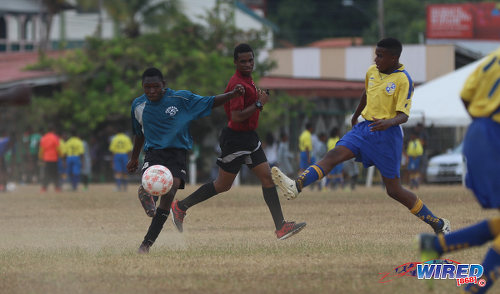 Photo: A Police FC player (left) takes a crack at the Defence Force/SKHY FC goal during RBNYL Under-15 action at Constantine Park in Macoya on 6 May 2017. (Courtesy Sean Morrison/Wired868)
